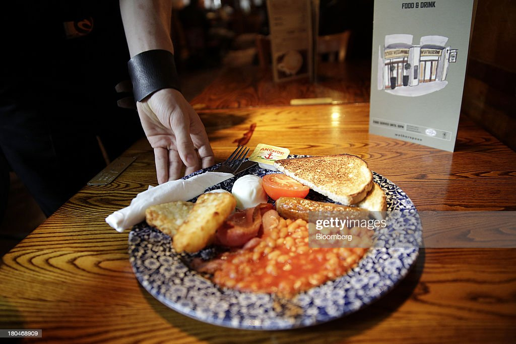 Wetherspoon Plc employee serves a full English cooked breakfast to a customer in this arranged photograph taken inside one of the company's pubs in London, U.K., on Friday, Sept. 13, 2013. JD Wetherspoon, who reported full year sales today, are planning to move into the Irish market next year, Chairman Tim Martin said in a recent interview. Photographer: Matthew Lloyd/Bloomberg via Getty Images