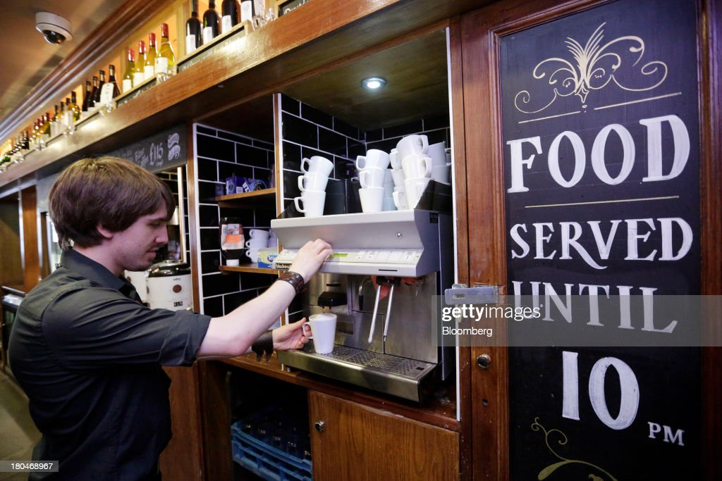 Wetherspoon Plc employee uses a coffee machine to make a hot drink for a customer inside one of the company's pubs in London, U.K., on Friday, Sept. 13, 2013. JD Wetherspoon, who reported full year sales today, are planning to move into the Irish market next year, Chairman Tim Martin said in a recent interview. Photographer: Matthew Lloyd/Bloomberg via Getty Images