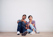 Shot of a young couple looking up while sitting against a white wall