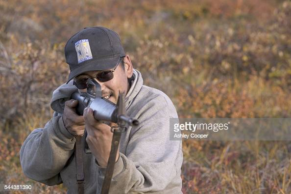 J J Weyiouanna uses his ancient rifle to hunt for Caribou on the Tundra Serpentine River mouth Alaska The way of life of the Inuit is threatened as...