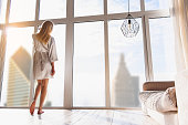 Relaxed young woman is enjoying urban view from window in her apartment. She is standing in white silk robe. Focus on her back