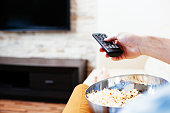 Close-up of a hand holding a remote control and a bowl of popcorn