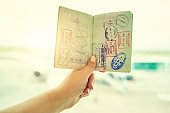 Shot of an unrecognizable person holding a passport indoors