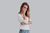 Curious young woman covering face with hand and looking at camera while standing against grey background