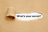 Question What Is Your Secret appearing behind ripped brown paper.