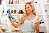 Cheerful young woman holding two different shoes and smiling white standing in the shoe store
