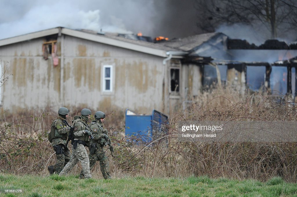 A Whatcom County Sheriff's Department SWAT team surrounds a burning house and a barn on Wednesday, February 13, 2013, north of Ferndale, Washington. Law enforcement officals were searching for the owner, Kenneth Cassell, who is suspected setting the house on fire.