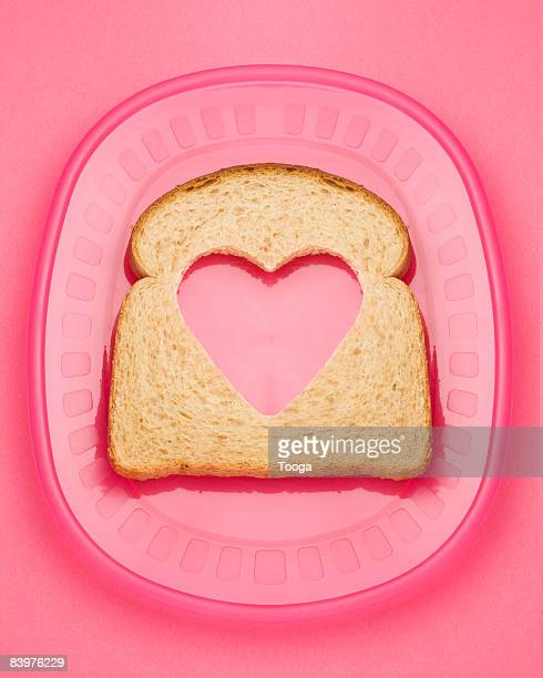 Wheat bread with heart cut out of it on pink plate