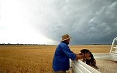 A wheat farmer pats his dog on his farm near Temora in NSW 6 December 2006 AFR Picture by LOUISE KENNERLEY