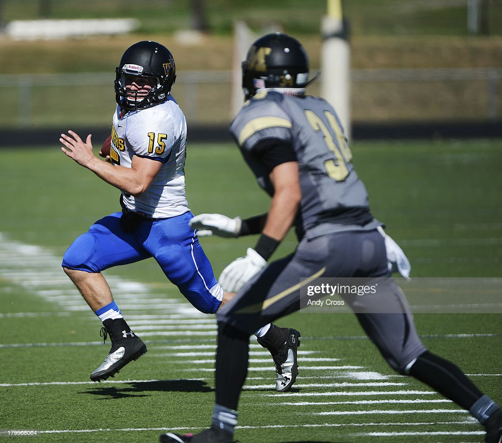 Wheat Ridge QB, Tanner Weakland, left, looks for running room on a keeper against Kidd Sole, Monarch High, in the first quarter of play at the Howard Spangenberg Field in Lafayette Colorado, Saturday morning, September 07, 2013.