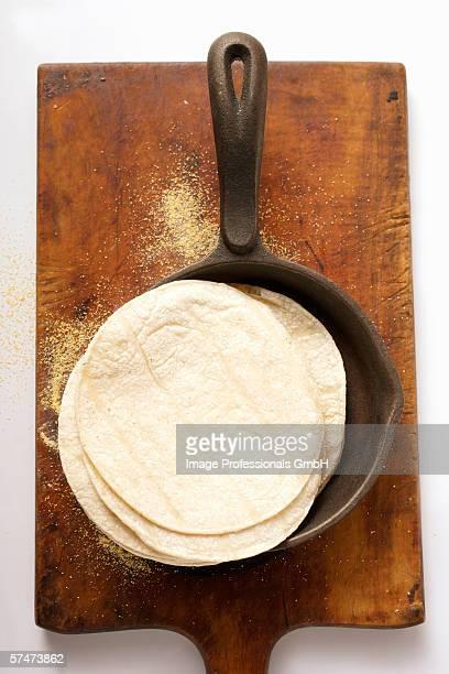 Wheat tortillas in frying pan on chopping board