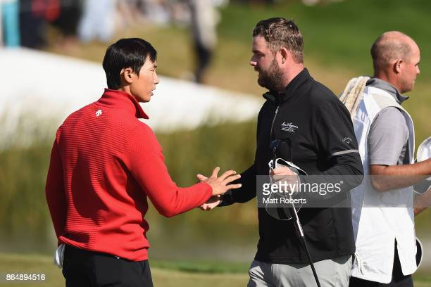 Whee Kim of South Korea and Marc Leishman of Australia shake hands on the 18th green during the final round of the CJ Cup at Nine Bridges on October...