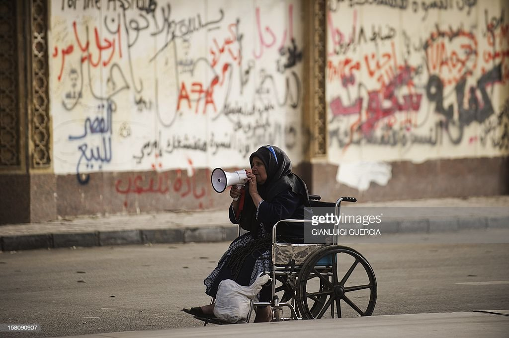 A wheel chair-bound woman shouts political slogans outside the presidential palace area on December 10, 2012 in Cairo. President Mohamed Morsi has ordered Egypt's army to 'cooperate' with police and given it powers of arrest until the results of a referendum to be held this weekend, according to a decree obtained by AFP. The decree, which appears in the government's latest official gazette under 'Law 107', was issued ahead of rival mass protests called by pro- and anti-Morsi camps over the referendum.