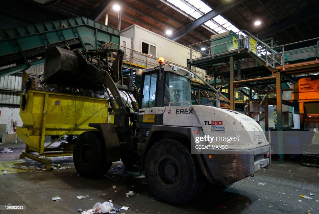 A wheel loader fill a container with garbage for recycling at a waste treatment plant in Burgos on January 18, 2013.