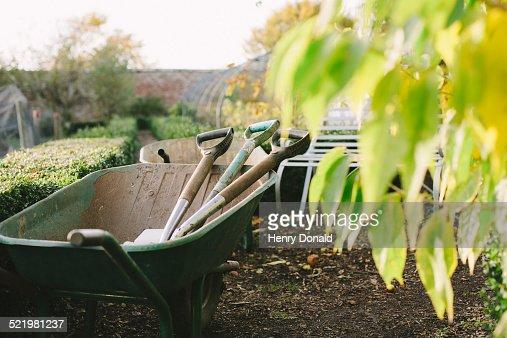 Wheelbarrow and spades in kitchen garden