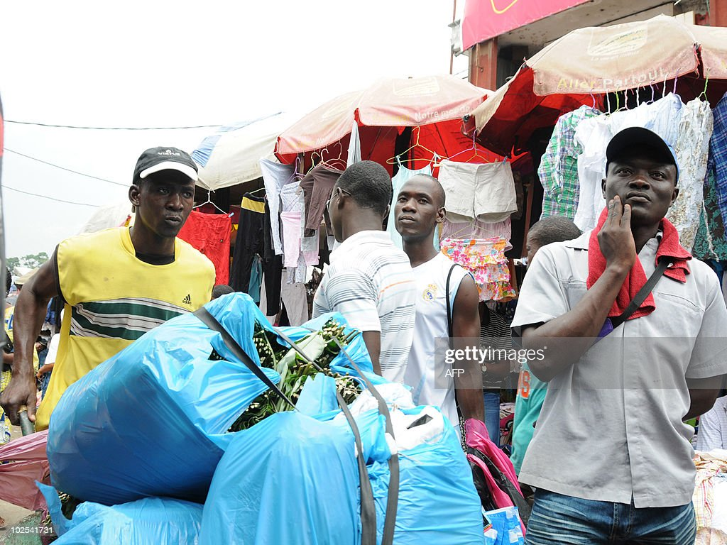 A wheelbarrow taxi man transports a client's shopping bags made from nonrecyclable blue plastic bags in a market in Libreville on June 29 2010 'It is...