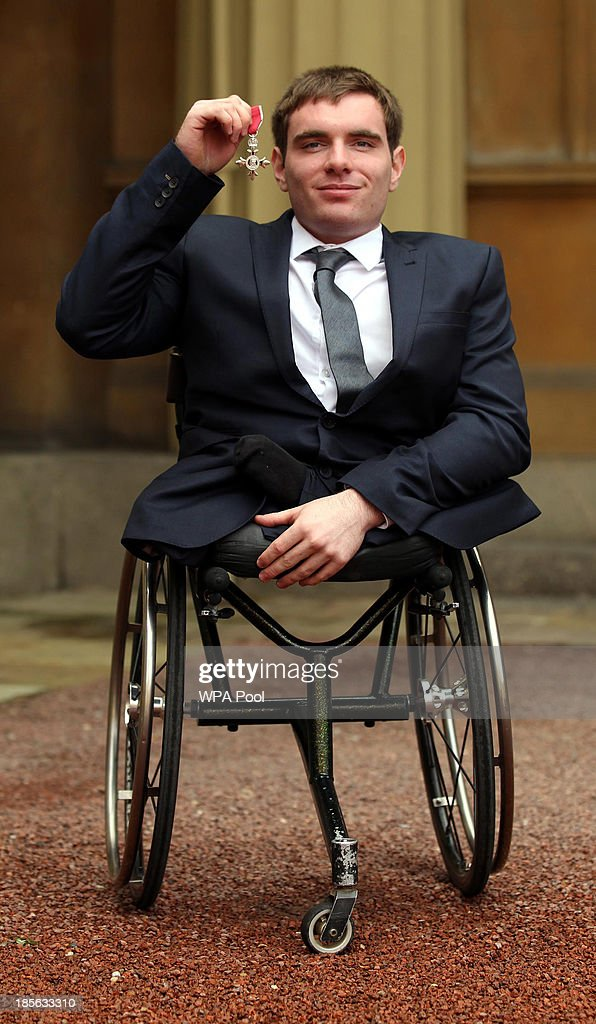 Wheelchair Athlete Michael Bushell holds his medal after being made a Member of the Order of the British Empire (MBE) by the Prince of Wales during an Investiture ceremony on October 23, 2013 at Buckingham Palace, London, England.