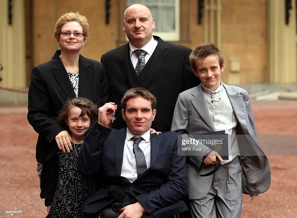 Wheelchair Athlete Michael Bushell poses with family members (names not given), as he holds his medal after being made a Member of the Order of the British Empire (MBE) by the Prince of Wales during an Investiture ceremony on October 23, 2013 at Buckingham Palace, London, England.