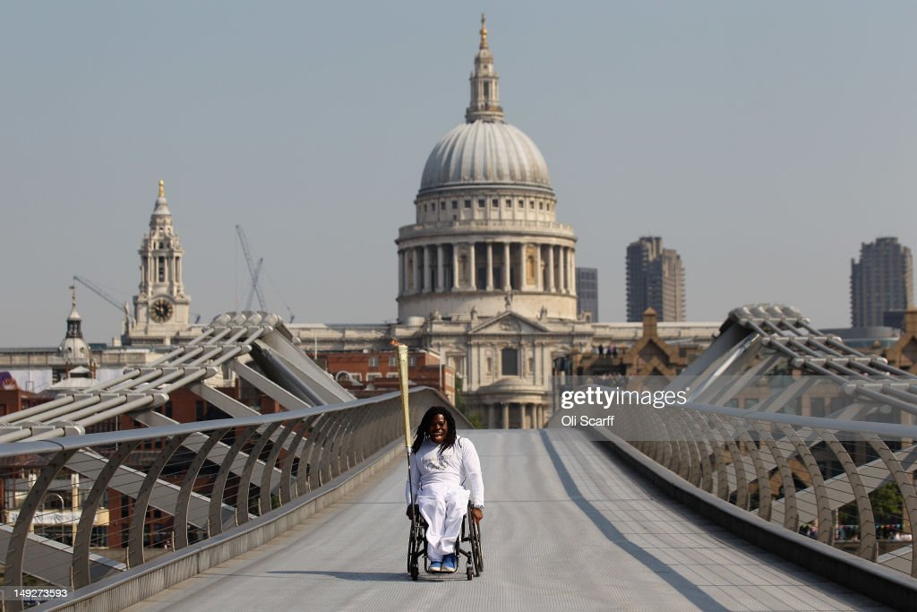 Wheelchair basketball player Adedoyin Adepitan carries the Olympic flame over Millennium Bridge in front of St Paul's Cathedral during Day 69 of the London 2012 Olympic Torch Relay on July 26, 2012 in London, England. The Olympic flame is making its way through the capital on the penultimate day of its journey around the UK before arriving in the Olympic Stadium on Friday evening for the Olympic games' Opening Ceremony.