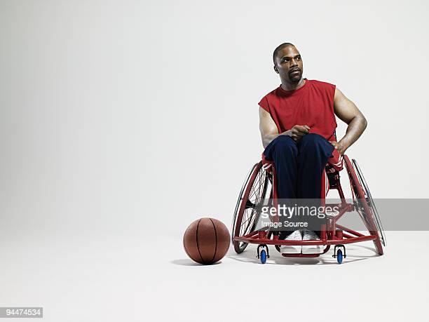 Wheelchair basketball player and ball on floor