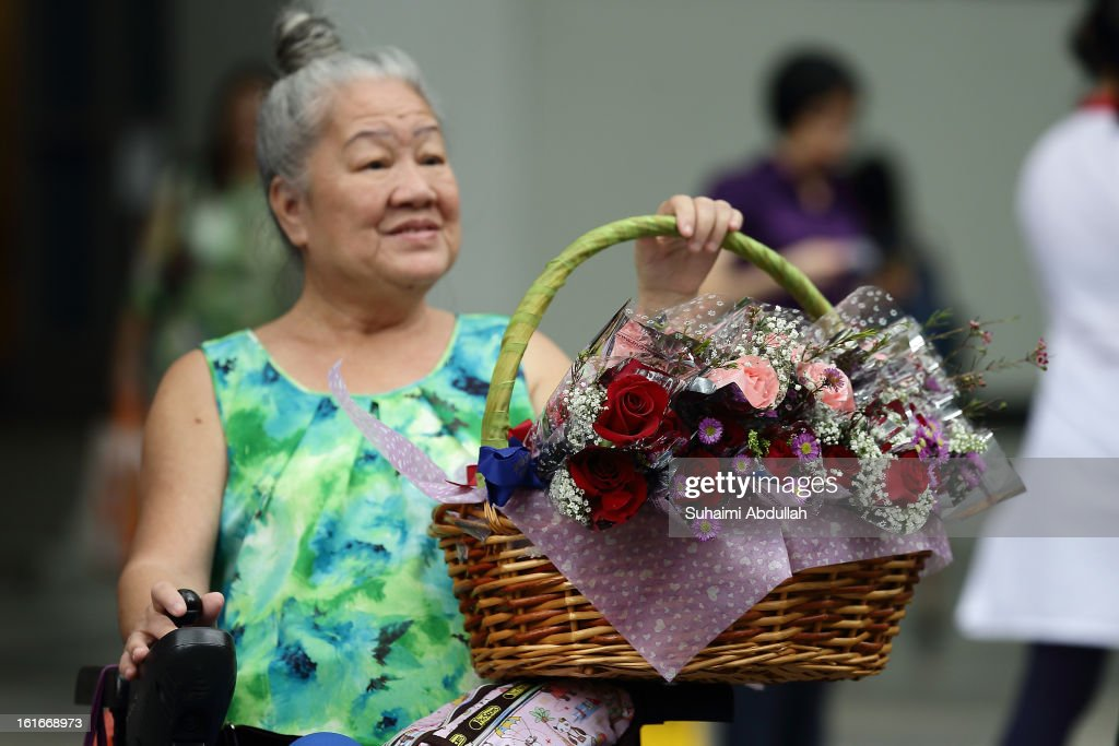 A wheelchair bound elderly woman sells flowers during Valentine's Day at Raffles Place on 14 February, 2013 in Singapore. Valentine's Day is a time to celebrate love, romance and friendship and is celebrated worldwide annually in different ways on February 14.