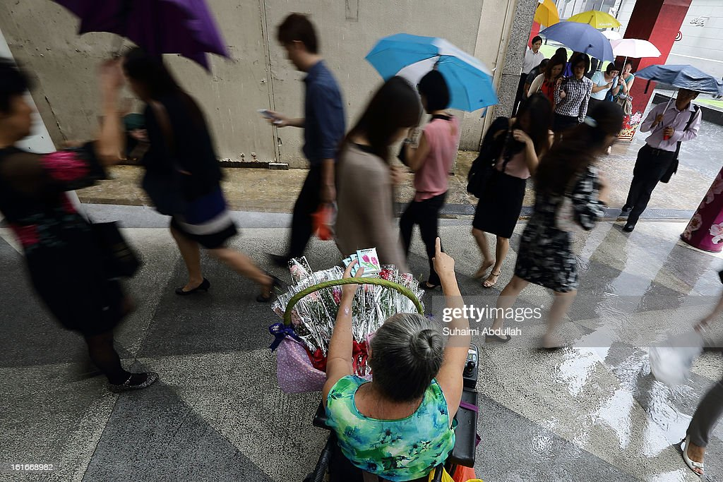A wheelchair bound elderly woman tries to sell her flowers during Valentine's Day at Raffles Place on 14 February, 2013 in Singapore. Valentine's Day is a time to celebrate love, romance and friendship and is celebrated worldwide annually in different ways on February 14.