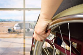 rear view of a woman in wheelchair at the airport with focus on hand