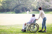 Taking a wheelchair old man and a helper in the park