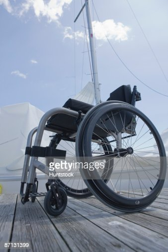 Wheelchair on jetty, yacht in background : Stock Photo