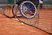 Unfocused wheelchair tennis player seen behind a tennis net on a clay court