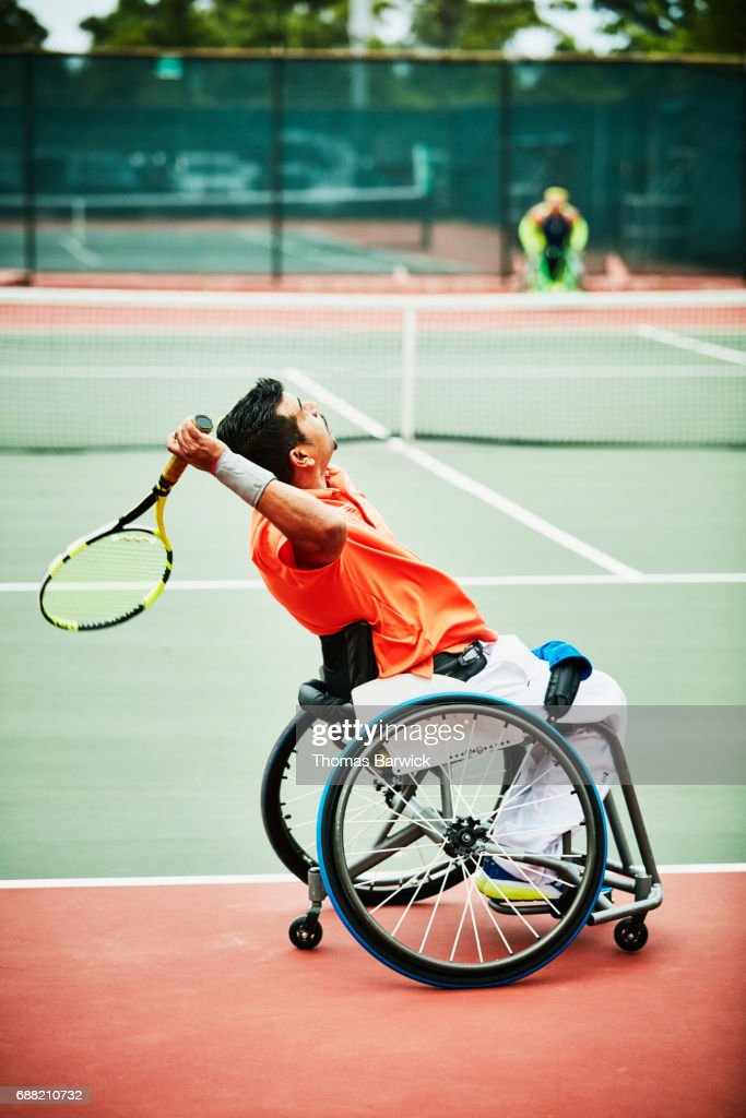 Wheelchair tennis player serving during match : Stock Photo