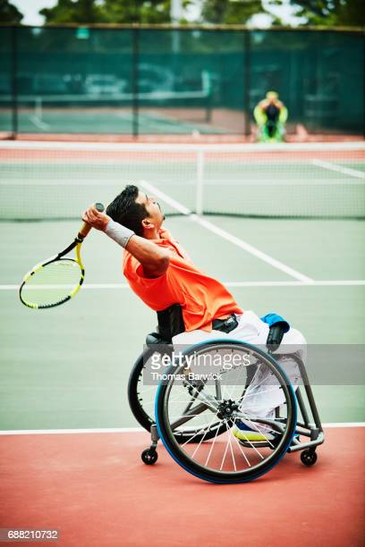Wheelchair tennis player serving during match