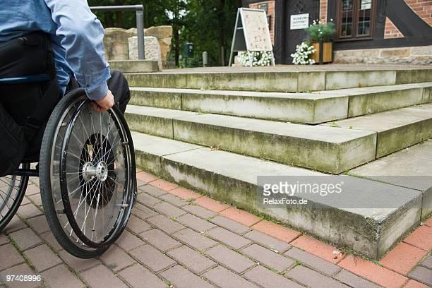 Utilisateur en fauteuil roulant en face de l'escalier barrière (XXL