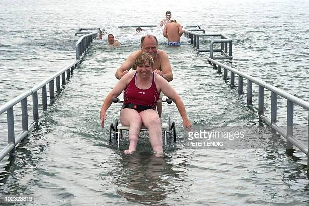 Wheelchair user Martina Scholz is pushed by Rolf Sondershaus of the Leipzig Association for Handicapped People as she tries out a new handicapped...