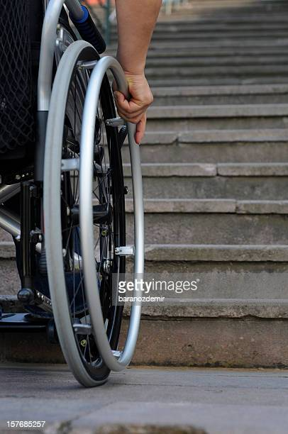 Wheelchair user stand near the stairs