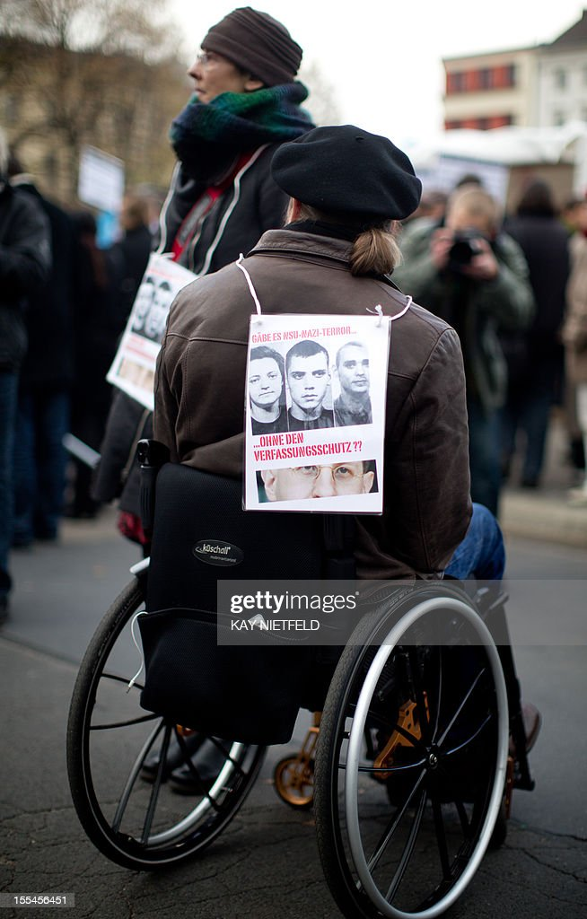 A wheelchair user wears a poster with the portraits of the alleged committers of a murder spree targeting immigrants during a protest march against racism on November 4, 2012 in Berlin. Twelve months after revelations that a neo-Nazi trio was likely behind the seven-year murder spree in which nine men of Turkish and Greek origin and a German policewoman were killed, Germany has sought to mend security flaws but the trauma still reverberates.