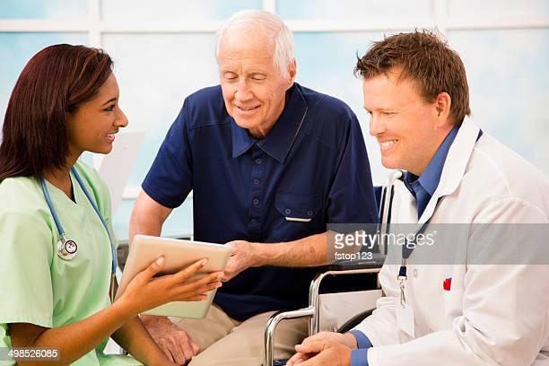 Rollstuhl-bound senior Patienten mit einer Krankenschwester, Arzt.  Digitale tablet.