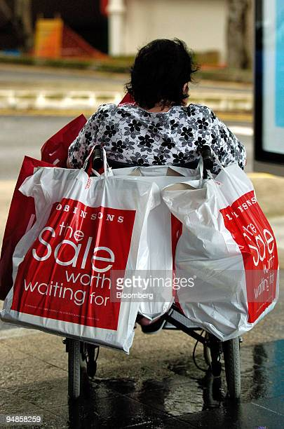 A wheelchairbound woman watches over her family's shopping bags Saturday January 1 2005 in a Singapore shopping district The government announced on...