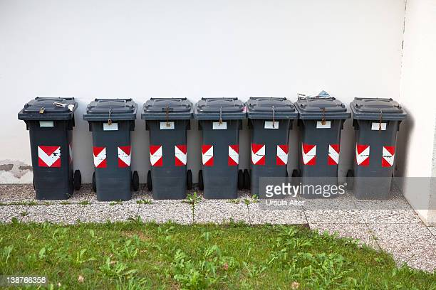 wheeled garbage cans in a row
