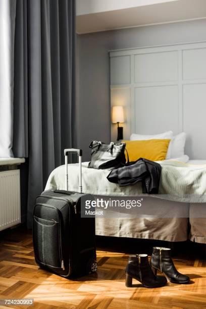 Wheeled luggage and womenswear in hotel room