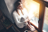 Top view of beautiful young woman looking through window while sitting at windowsill at home