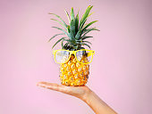 Cropped shot of a woman holding a pineapple with glasses on against a white background