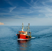 """A trawler returns to the harbour at West Bay, Dorset. East Cliff just appears in the left of the frame"""