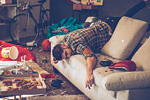 Young handsome man passed out on sofa in messy room after party
