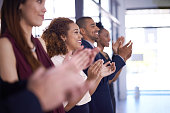 Closeup shot of a group of businesspeople clapping while standing in a row in an office