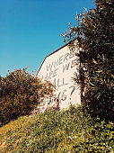 """""""where are we all going?"""" is handwritten on the facade of a house in the countryside. *** The text was digitally superimposed and a release is provided ***"""