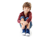 Studio shot of a cute little boy hugging his knees against a white background