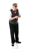 Full-length image of a senior conductor holding out his pocket watch while anxiously looking for the train.  On a white background.