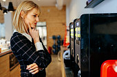 Blonde businesswoman standing in front of a coffee maker in an office cafeteria