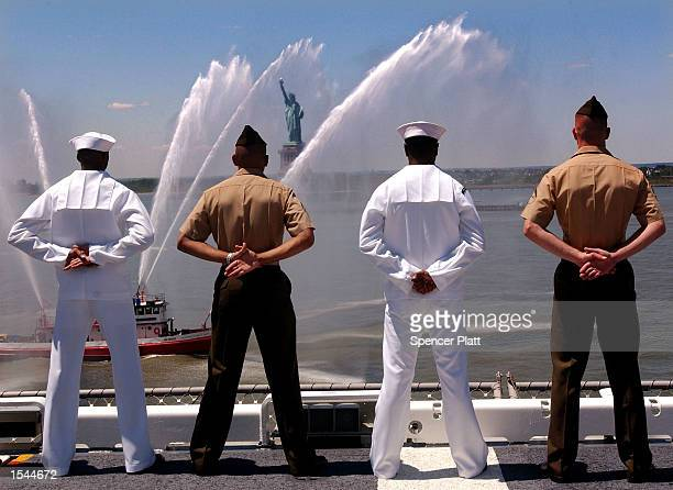 While a fire boat shoots water in the air US Navy sailors stand with US Marines aboard the USS Iwo Jima May 22 2002 as the ship passes the Statue of...